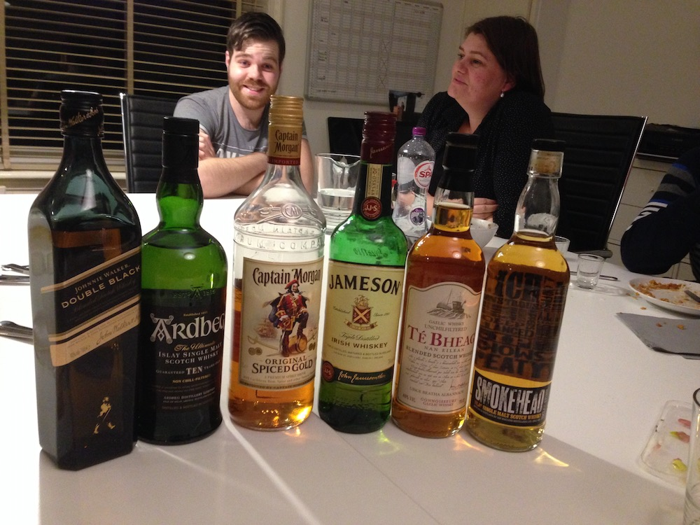 Five bottles of whisky and one bottle of rum lined up at an #a11y meeting, Tim and Iacobien in the background.